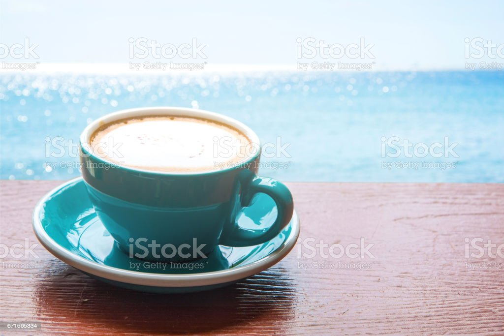 Close up cup of coffee on wood table and blue sea background. stock photo