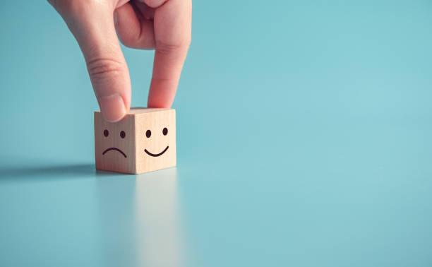 close up customer hand choose smiley face and sad face icon on wood cube, service rating, satisfaction concept, copy space. - emoção positiva imagens e fotografias de stock
