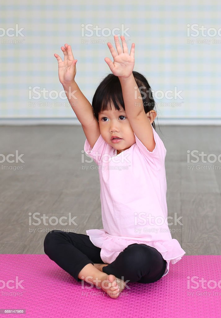 Close up Cute toddler girl practicing yoga or doing exercise stock photo