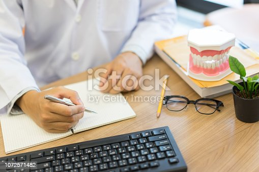 close up dentist hand wiring knowledge on notebook after learning about  teeth treatment inside oral  for study case of patient at clinic office table , dentistry medical concept