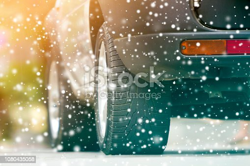 istock Close up detail car wheel with new black rubber tire protector on winter snow covered road. Transportation and safety concept. 1080435058