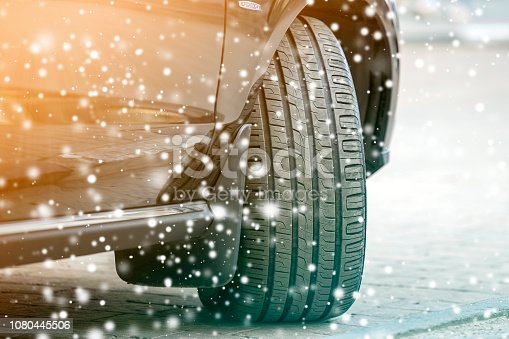 istock Close up detail car wheel with new black rubber tire protector on winter snow covered road. Transportation and safety concept. 1080445506