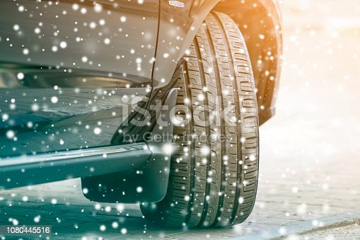istock Close up detail car wheel with new black rubber tire protector on winter snow covered road. Transportation and safety concept. 1080445516