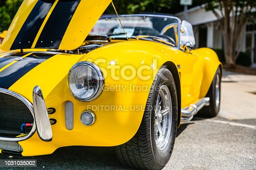 Matthews, North Carolina - September 3, 2018: Front view of a bright yellow Shelby Cobra parked on display with open hood at the Matthews Auto Reunion.