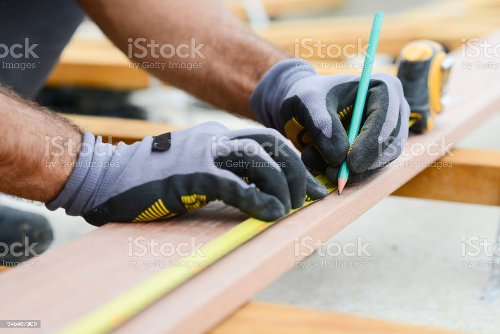 close up detail of manual worker hands working with a measuring tape and pencil in wood plank stock photo