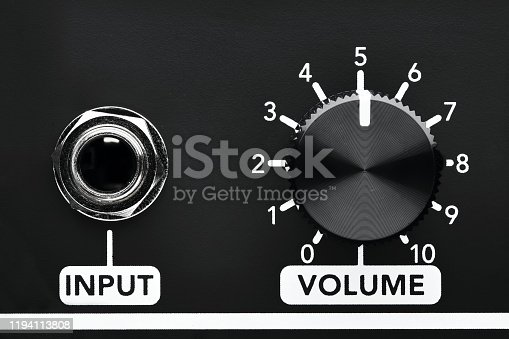 Close up detail of volume control knob and input jack of a black guitar amplifier. Close up view with copy space.