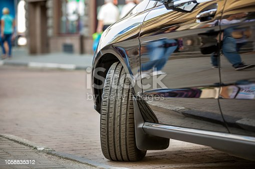 istock Close up detail part of car wheel with new black rubber tire protector on light blurred copy space background. Transportation, safety, reliability, modern design concept. 1058835312