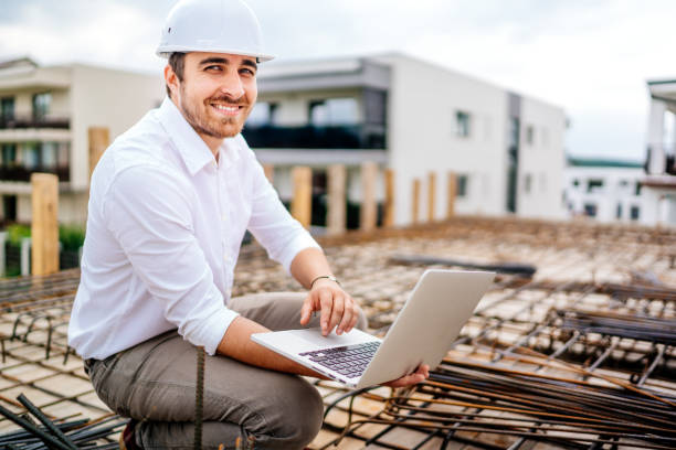 Close up details of architect using laptop on building construction site stock photo
