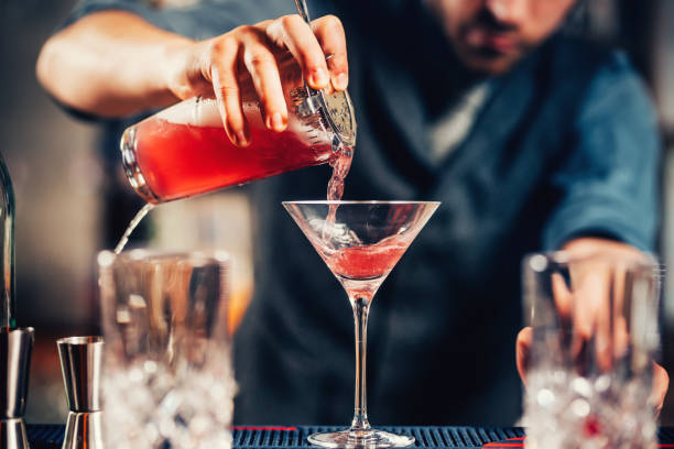 close up details of barman pouring vodka cosmopolitan cocktail in martini glass - bartender стоковые фото и изображения