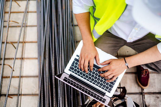 close up details of engineer working on laptop on construction site stock photo