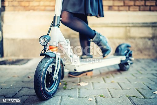 874772840istockphoto Close up details of modern transportation, electric kick scooter, Portrait of girl riding the city transportation 874772760