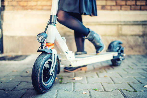 close up details of modern transportation, electric kick scooter, portrait of girl riding the city transportation - electric push scooter stock photos and pictures