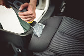 istock Close up details of worker vacuuming leather car interior 870884650