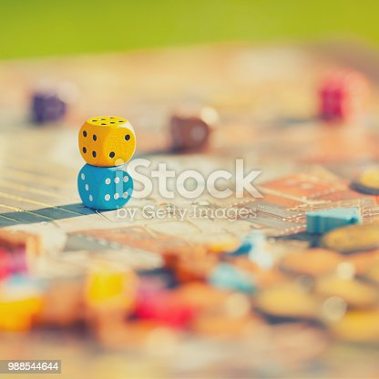 Closeup: dices at the table with Board game. Gameplay moments. Random game concept, toned photo.