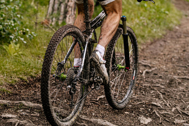 close up dirty feet cyclist and mountain bike stock photo