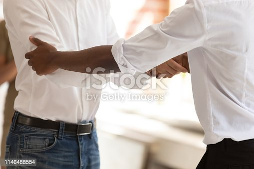 istock Close up diverse businessmen standing in office room shaking hands 1146488554