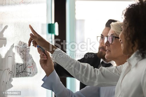 Close up diverse colleagues drawing on flip chart, brainstorming, planning, discussing strategy, working on project together, African American mentor teaching employees, analyzing graphs