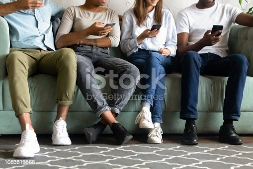 istock Close up diverse people sit couch, using mobile devices 1083813566