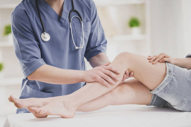 Close up. Doctor Comfforting Leg of Sitting Woman. stock photo