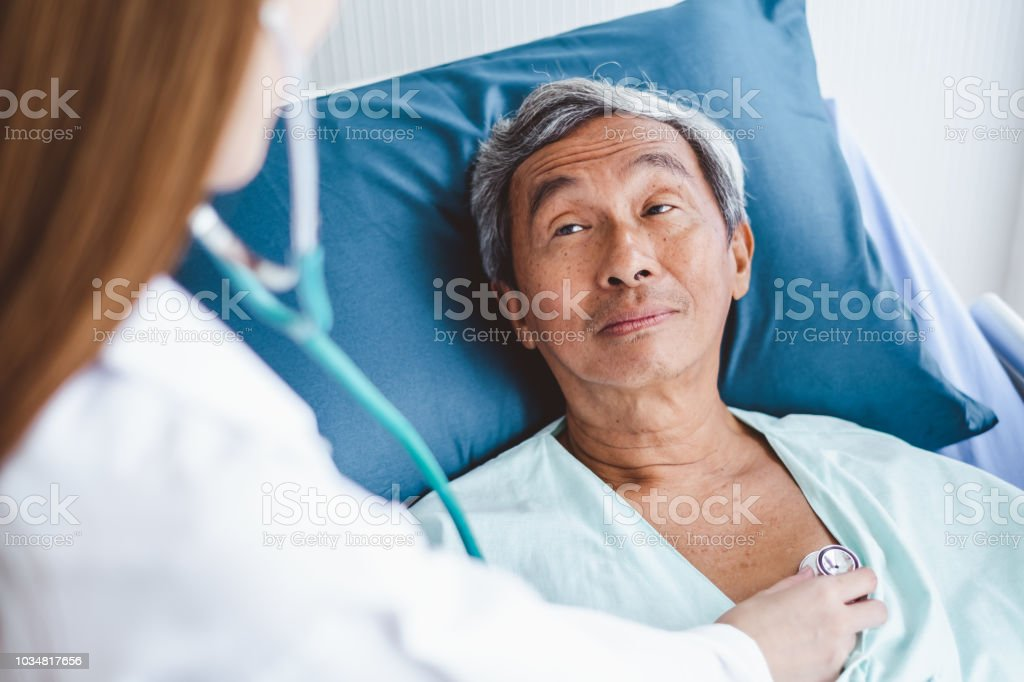 Close up doctor hand examining old asian patient by using stethoscope...