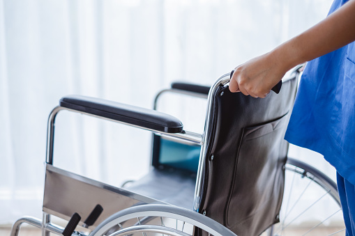 504241549 istock photo Close up doctor/nurse hand holding and pushing wheelchair for patient and medical concept 1019859902