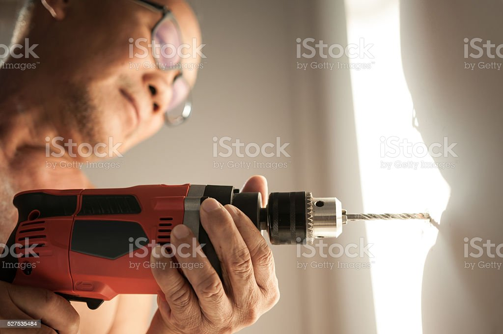 Close up drill, Old man using a drilling power tool stock photo