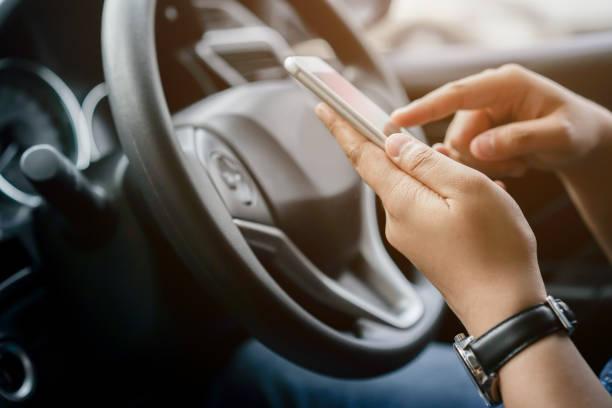 cerrar conductor mujer mano sosteniendo teléfono inteligente para el uso de la navegación gps de destino de viaje y deslizar para leer datos en el navegador web o mensajes de texto en línea para el contacto durante el estacionamiento, concepto de estilo - uso compartido del coche fotografías e imágenes de stock