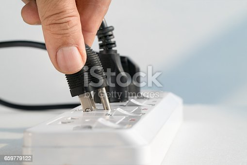 istock Close up Elderly hand plugging into electrical outlet 659779122