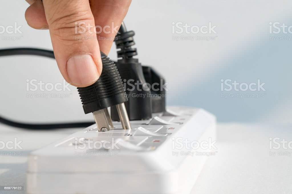 Close up Elderly hand plugging into electrical outlet stock photo