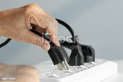 istock Close up Elderly hand plugging into electrical outlet 659779340