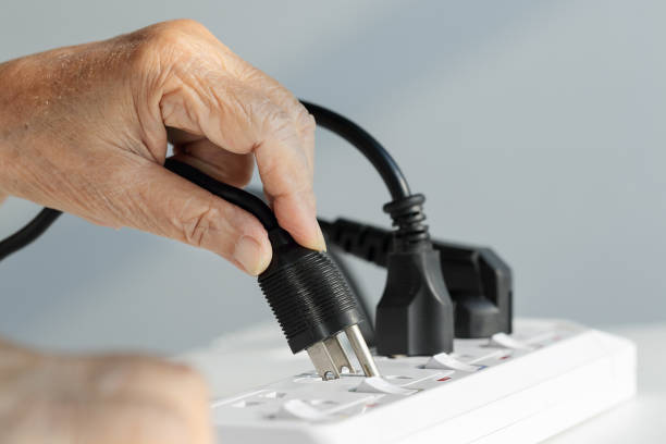 close up elderly hand plugging into electrical outlet - electrical outlet stock photos and pictures