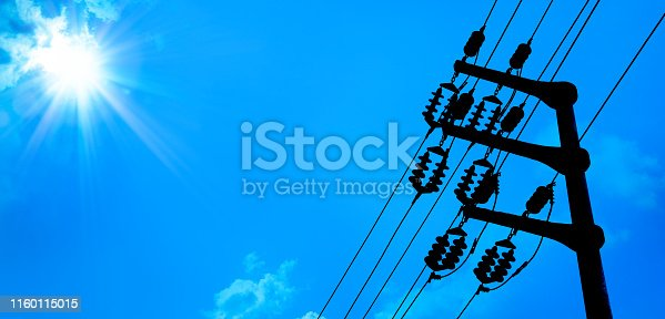 close up electricity power line tower over blue sunny sky with shining sun