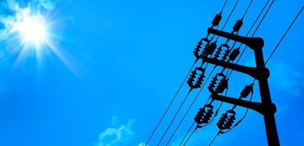 nahaufnahme stromleitungsturm über blauem sonnigen himmel - stromkabel stock-fotos und bilder