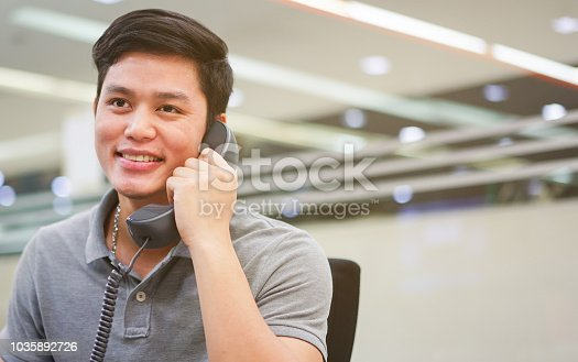 istock close up employee asian man holding handset from telephone for talking conversation with colleagues or answer customer , call enter concept 1035892726