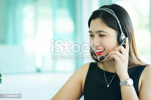 1142008983 istock photo close up employee call center woman agent wear headset device smiling and talking with customer on desktop pc table at operation room , telemarketing and help desk concept 1136685919