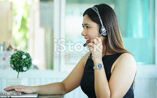 1142008983 istock photo close up employee call center woman agent wear headset device smiling and talking with customer with looking laptop on table at operation room , telemarketing and help desk concept 1138216274