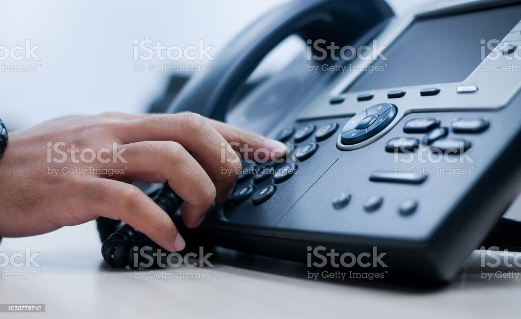 close up employee man hand point to press button number on telephone...