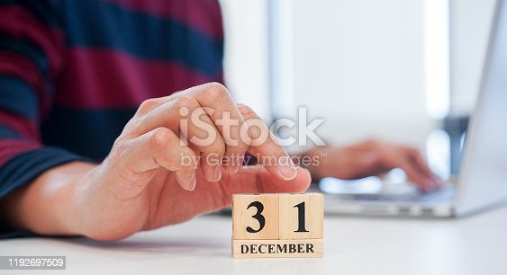 istock close up employee man hand put number 1 of cube shape wood to make calendar date December 31 at office desk for the last day of the last year countdown concept 1192697509
