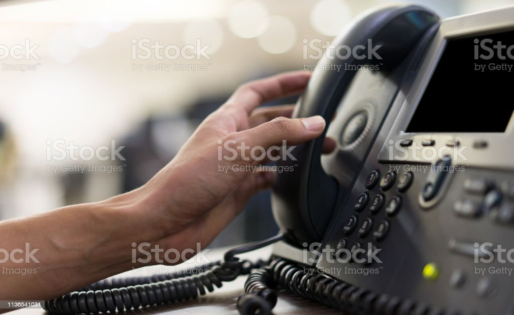 close up employee man hand touching handset of  telephone on desk for contact customer or receiving call , hotline  concept - Foto stock royalty-free di 24-7- Segnale Inglese