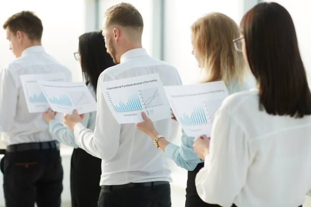 aus nächster Nähe. Mitarbeiter mit Finanzdaten stehen in einer Reihe – Foto