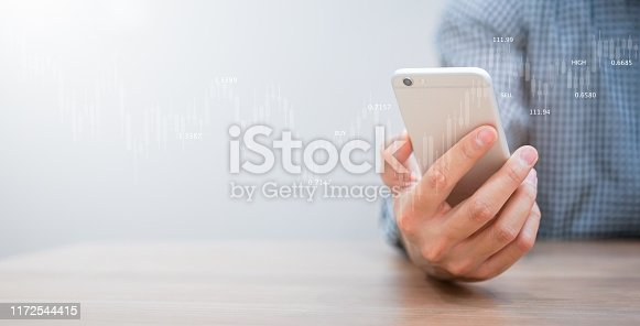 istock close up expert investor of  stock trader hand holding smartphone and monitoring trading board for forecasting about buying or selling currency exchange rate , business with technology concept 1172544415
