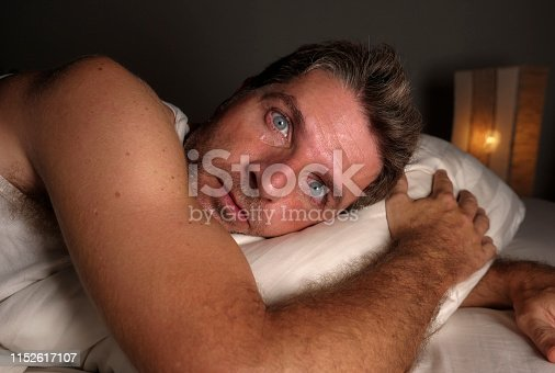 close up face portrait of sleepless and awake attractive man with eyes wide open at night lying on bed suffering insomnia sleeping disorder trying to sleep with dramatic facial expression