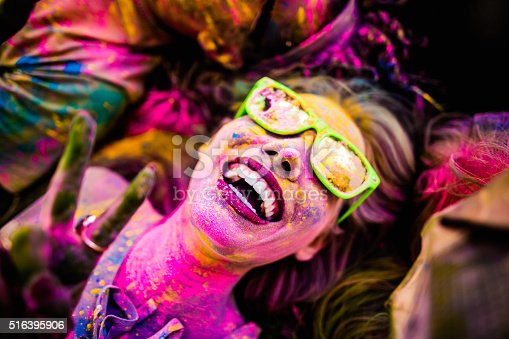 Close Up face shot of girl covered in colorful powder smiling and making peace sign while laying down on grass in a park during Holi Festival