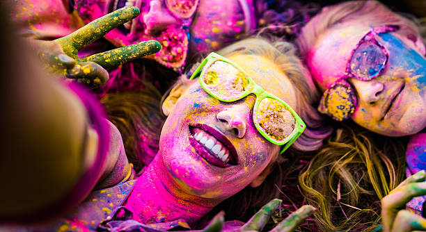 Close up Face Shot of Girl Covered in Holi Powder Close Up face shot of girl covered in colorful powder, smiling and taking a selfie while laying down on grass in a park during Holi Festival colored powder stock pictures, royalty-free photos & images
