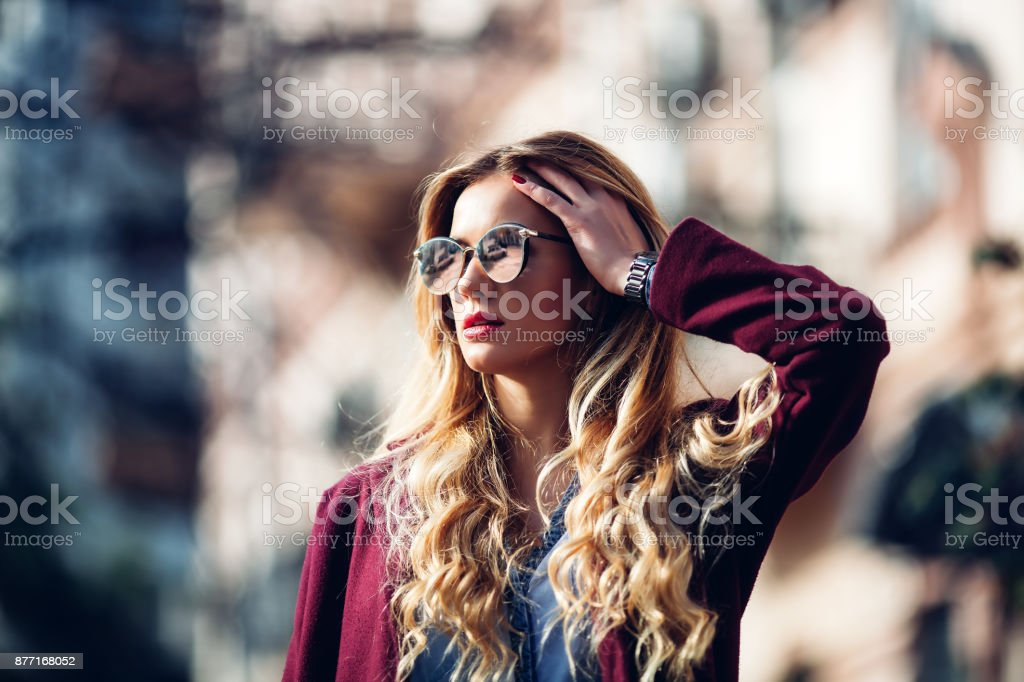 Close up fashion street stile portrait of pretty girl in fall casual outfit Beautiful blond posing outdoor. stock photo