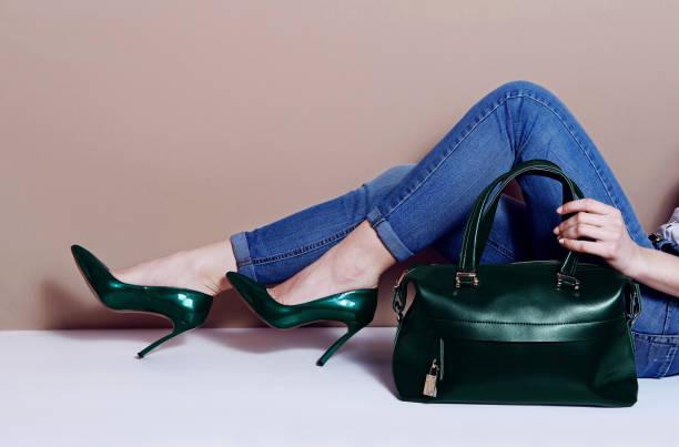 close up mode frau beine in grünen high heels und big bag - handtasche jeans stock-fotos und bilder