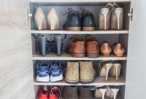 modische damen high heels, leder herrenschuhe und sportschuhe im holzgehäuse für den gang zum arbeiten hautnah - garderobe mit schuhschrank stock-fotos und bilder
