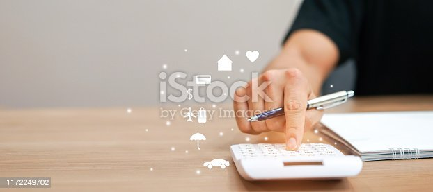 close up father hand pressing on calculator for calculating about spending monthly such as life insurance,home loan,travelling,credit card,savings money, at table in home for city lifestyle expenses concept