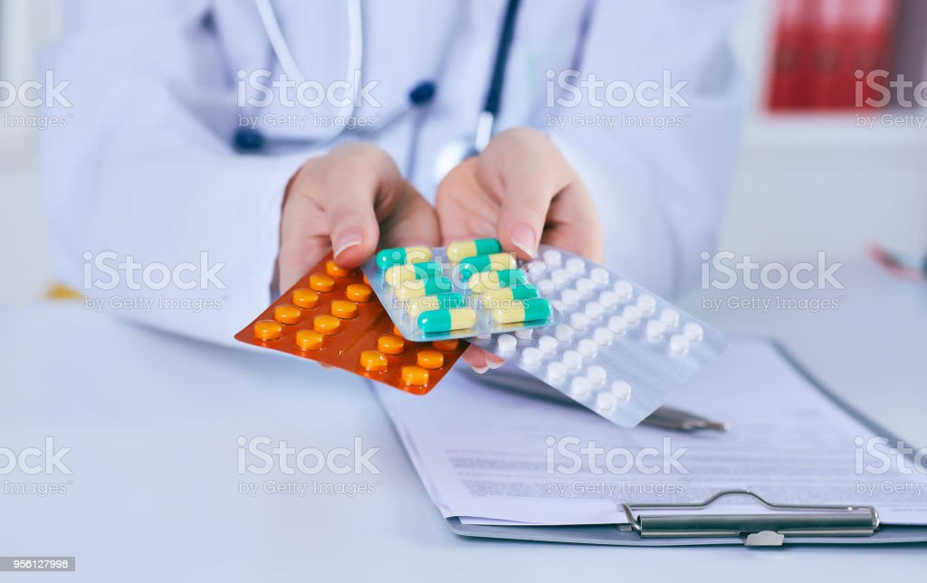 Close up female doctor hand holding pack of different tablet blisters. Life save service, legal drug store, prescribe medicament concept stock photo