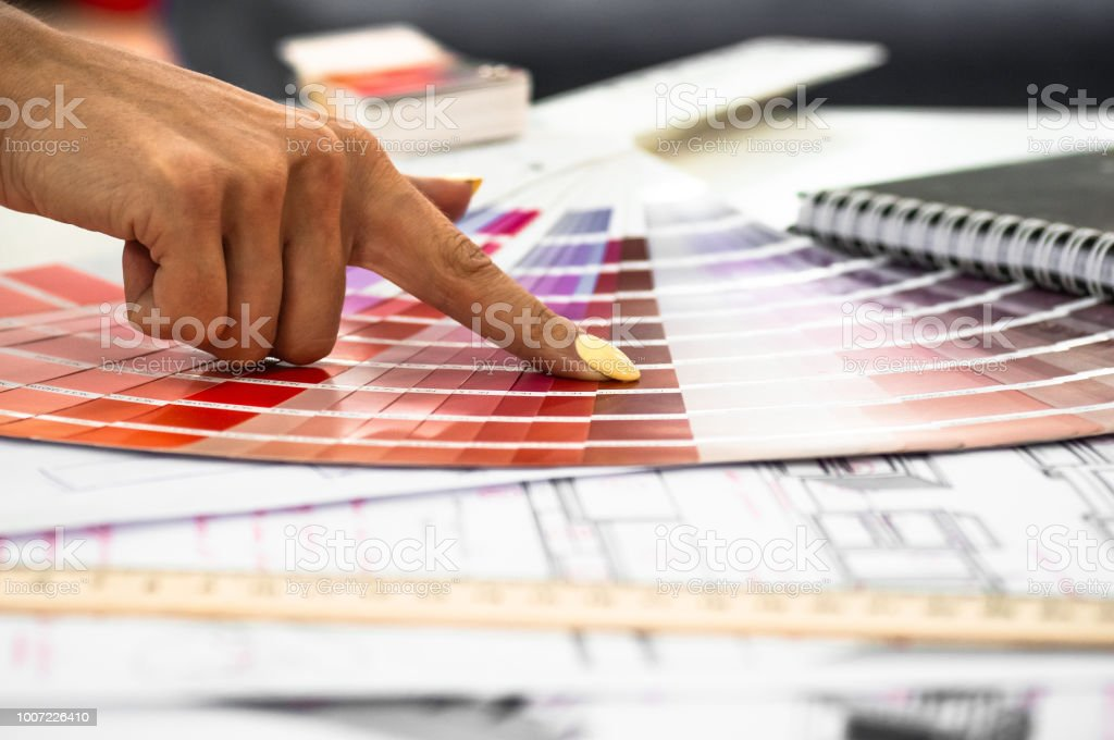 Close up female hand holding a Multicolored Samples for interior painting or furniture on the background for new construction or renovate home. Industry Production Concepts stock photo